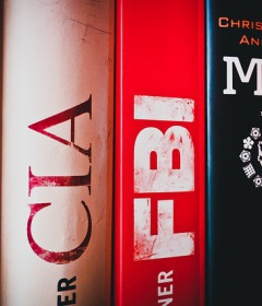 Image of book spines on a shelf about he CIA and FBI